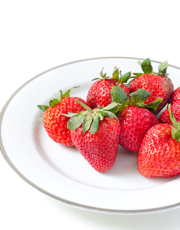 Ripe strawberries in a porcelain plate on white background photo