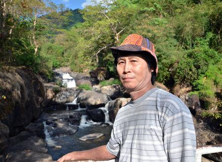 Senior man enjoying the waterfall, outdoor portrait photo