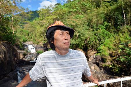 Senior man enjoying the nature with beautiful waterfall in background photo