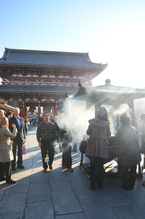 TOKYO, JAPAN - NOVEMBER 21  Buddhists gather around a fire to light incense and pray at Sensoji Temple on November 21, 2013 in Tokyo, Japan