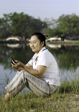 Happy woman listening to music in park photo