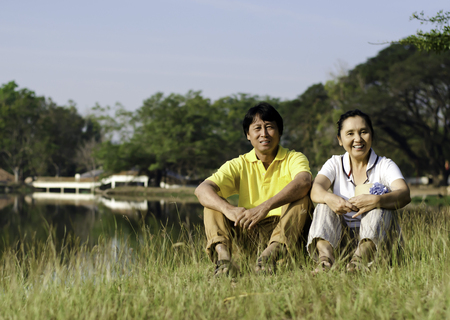 Portrait of beautiful couple sitting on grass in park   photo