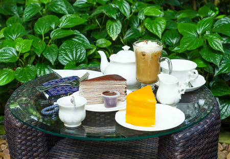 chocolate crape cake and orange cake on table in garden photo