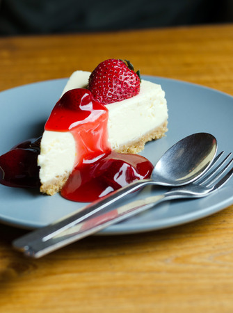 Fresh Strawberry Cheesecake with spoon and fork on dish photo