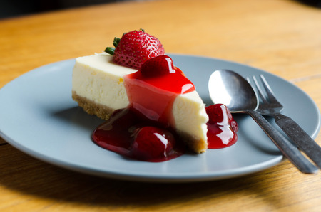 Strawberry Cheesecake with spoon and fork on wooden table photo