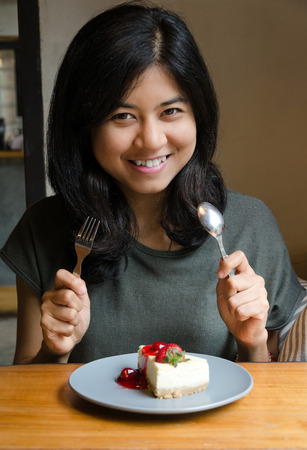Young beautiful asian woman with a cake in cafe photo