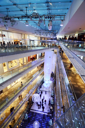 Tokyo, Japan - November 24, 2013: People shopping in Omotesando Hills on november 2013. 24,  Omotesando Hills consists of six floors (three are underground) of about 100 upmarket shops, cafes, restaurants and beauty salons.