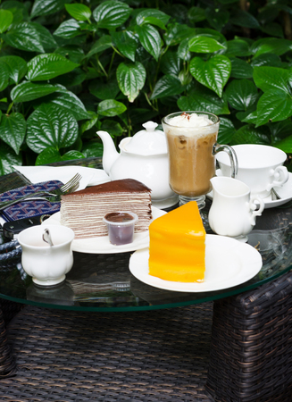 Coffee, tea, chocolate crape cake and orange cake on table in outdoor garden photo