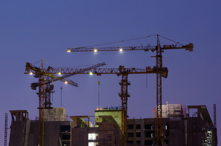 Industrial construction cranes in twilight time photo