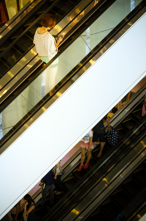 Bangkok, Thailand - September 12, 2013: Shoppers on escalator at Terminal21 shopping mall on September 12, 2013. Terminal21 is a new shopping mall in the Asok district in Bangkok, Thailand