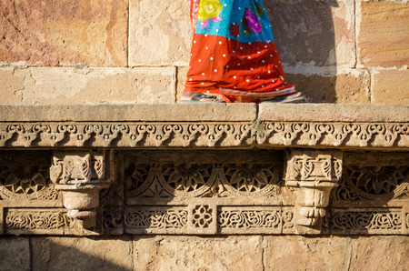 toran: Indian woman walking on beautiful border patterns & designs engraved on the stone wall & frieze Stock Photo