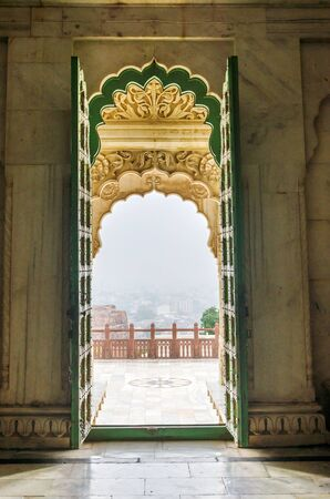 ornately: Entrance Gate of Jaswant Thada. Ornately carved white marble tomb of the former rulers of Jodhpur, India