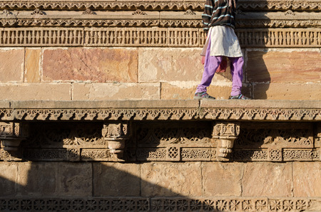 toran: Indian woman walking on beautiful border patterns & designs engraved on the stone wall of Adalaj Stepwell, Ahmedabad, India
