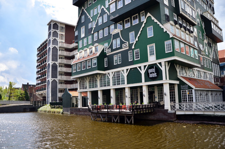zaan: Zaandam, Netherlands - May 5, 2015: Tourist visit Inntel Hotels on May 5, 2015 in Zaandam, Netherlands. Opened in 2009, the design attracts guests by incorporating the traditional architecture of the Zaan region. Editorial