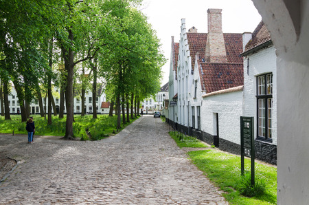 catholic nuns: Bruges, Belgium - May 11, 2015: People visit White houses in the Beguinage (Begijnhof) in Bruges, Belgium. In 1937 the beguinage became a monastery for the Benedictine sisters who still live here now. Editorial