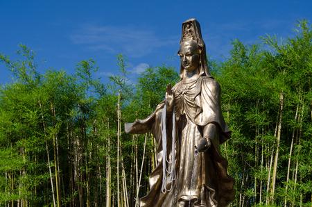 mercy: Guan Yin, Goddess of Mercy, bronze statue in Bamboo Garden Stock Photo