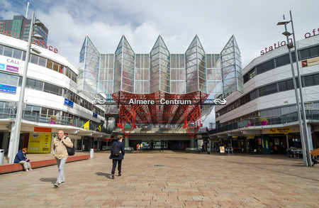 almere: Almere, Netherlands - May 5, 2015: People visit Almere Central Station on May 5, 2015 in Almere, Netherlands. The station opened may 1987 and is designed by Peter Kilsdonk. Under the station lies a bus station Editorial
