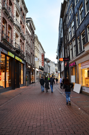 priced: Amsterdam, Netherlands - May 7, 2015: Unidentified people Shopping on Kalverstraat, main shopping street of Amsterdam. Kalverstraat is usually crowded with many shops selling competitively priced products.