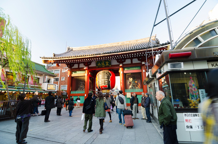 approached: Tokyo, Japan - November 21, 2013: Tourists at the entrance of Sensoji temple. The temple is approached via the Nakamise, shopping street, providing tourist souvenirs.