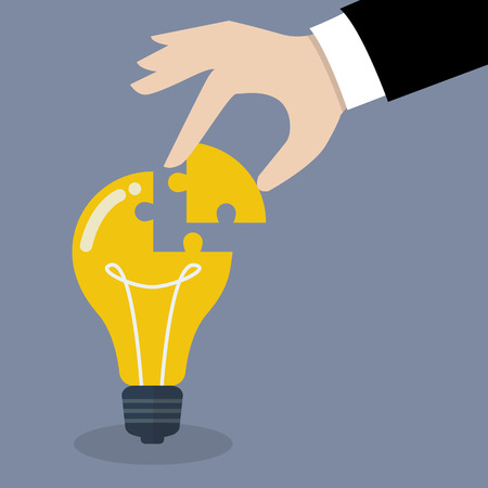 complete: Hand inserts the missing puzzle in lightbulb. Business idea concept