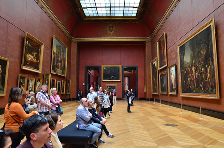 consistently: Paris, France - May 13, 2015: Visitors visit Rubens paintings in Louvre Museum, Paris, France. With 8.5 m annual visitors, Louvre is consistently the most visited museum worldwide.