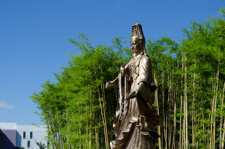 goddess of mercy: Guan Yin, Goddess of Mercy, bronze statue with Bamboo Garden in background