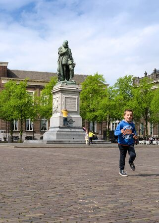 plein: The Hague, Netherlands - May 8, 2015: Children at Het Plein in The Hagues city centre, with the statue of William the Silent in the middle. on May 8, 2015.
