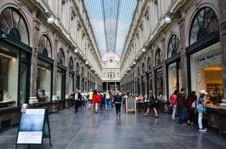 preceded: Brussels, Belgium - May 12, 2015: Tourists shopping at The Galeries Royales Saint-Hubert in Brussels, Belgium. This place is a glazed shopping arcade in Brussels that preceded other famous 19th-century shopping arcades.