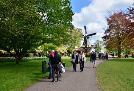 lisse: Lisse, The Netherlands - May 7, 2015: Old windmill with many tourists in famous garden in Keukenhof. Keukenhof is the most beautiful spring garden in the world. Editorial