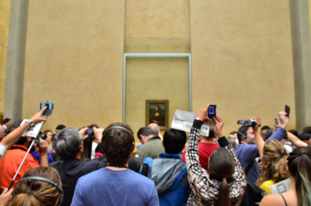 mona lisa: Paris, France - May 13, 2015: Visitors take photos of Leonardo DaVincis Mona Lisa at the Louvre Museum on May 13, 2015 in Paris, France. The painting is one of the worlds most famous, shallow depth of focus.