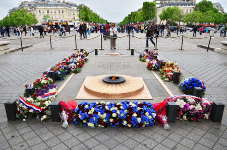 beneath: Paris, France - May 14, 2015: Tourist visit Tomb of the Unknown Soldier beneath the Arc de Triomphe, Paris. on May 14, 2015.