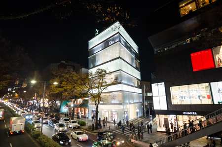 omotesando: Tokyo, Japan - November 24, 2013: Tourists shopping on Omotesando Street at night on November 24. 2013, Omotesando street sometimes referred to as Tokyos Champs-Elysees. Here you can find famous brand name shops, cafes and restaurants for a more adult cl