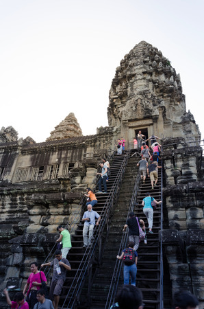 kingly: Siem Reap, Cambodia - December 4, 2015: Tourists climb to a praying tower at Angkor Wat. The temple is at the top of the high classical style of Khmer architecture. It has become a symbol of Cambodia,