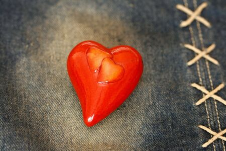 Red ceramics heart on denim cloth