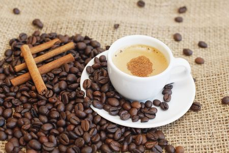 Mug with coffee coffee and coffee beans on the juta background