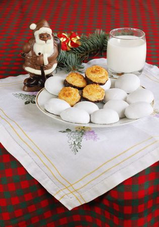 Chocolate Santa Claus with coconut and ginger cookies and glass of milk at background photo
