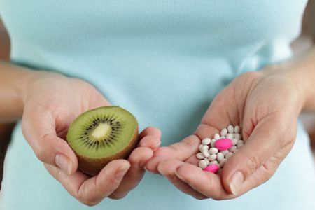 Mature woman hands and her choice -  pills or fruit Stock Photo