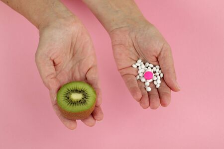menopause: Mature woman hands and her choice -  pills or fruit Stock Photo