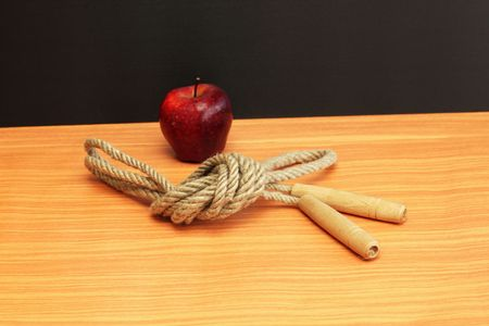 Skipping-rope and apple on a wallpaper