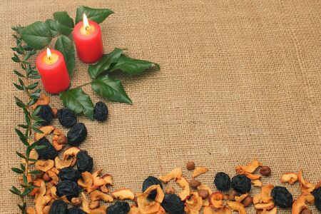 Burlap with lighting candles and branches of holly tree  Stock Photo