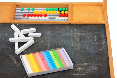 White and colored chalks on the old blackboard with abacus photo