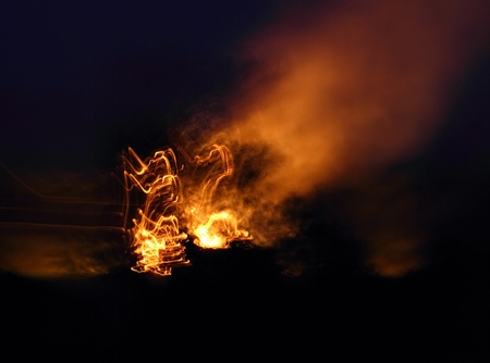 Abstract - stack of hay in fire near the village