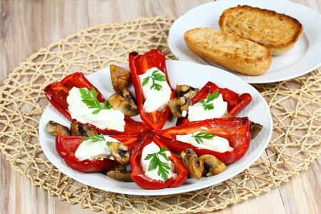 baguet: Stuffed grilled pepper.Pepper filled with cream cheese. Red stuffed pepper. Grilled pepper on the plate. Stock Photo