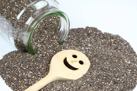 hispanica: Organic dry chia seeds. Glass of chia seeds. Chia seeds on white background. Chia seeds with funny stirring spoon. Healthy chia seeds. Seeds of salvia hispanica. Stock Photo