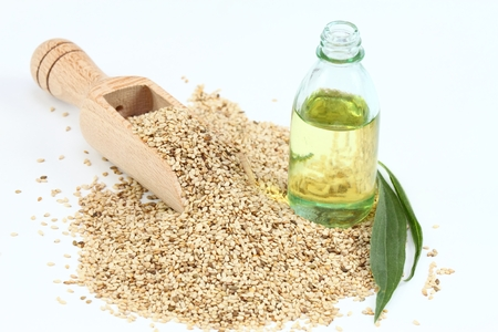 white sesame seeds: Organic unpeeled white sesame seeds and sesame oil. White sesame seeds in wooden spoon. Sesame seeds and oil on white background.