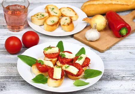 baguet: Grilled open sandwich with  tomato and  cheese decorated with spinach leaves, parsley