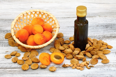 Aprikosenöl aus Aprikosenkernen in einer braunen Flasche, Aprikosenkerne herum und frische Aprikosen in einem Korb auf Holztisch