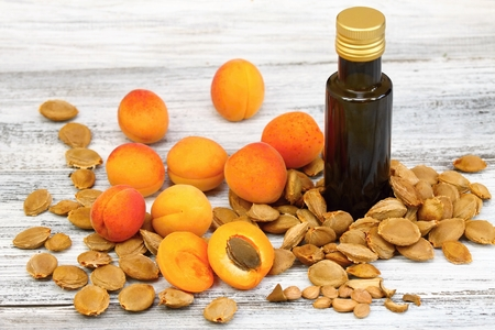 pip: Apricot oil from  apricot kernels in a brown bottle , apricot seeds around  it and  fresh apricots on wooden table