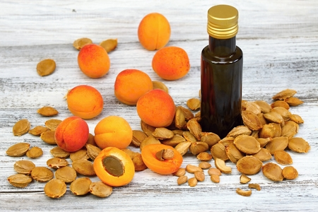 apricot kernels: Apricot oil from  apricot kernels in a brown bottle , apricot seeds around  it and  fresh apricots on wooden table