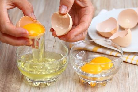 huevo blanco: Manos de la mujer que rompe un huevo para separar blanco y la yema de huevo y las cáscaras de huevo en el fondo